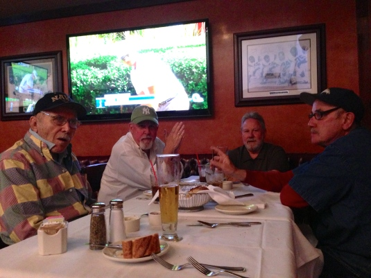 Dad and brothers dining in near darkness, illuminated only by the golf match on TV