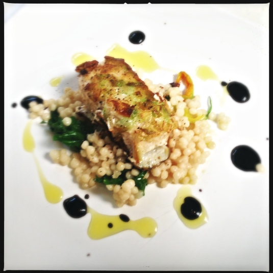 Scallion-crusted wolf fish with beurre blanc and wild greens Israeli cous cous