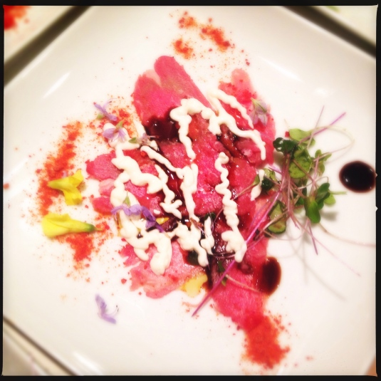 Prime tri-tip carpaccio, crackled black pepper frico, tomato powder, black & white sauces, tiny greens, flowers