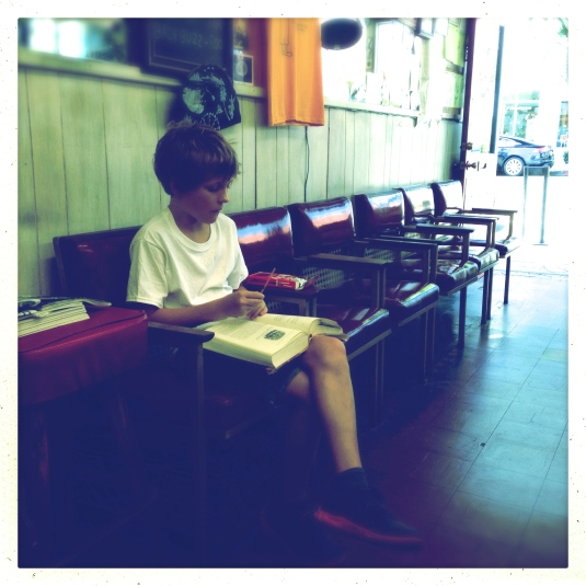 Flynn at the barber shop with his book while Dad gets his hair cut
