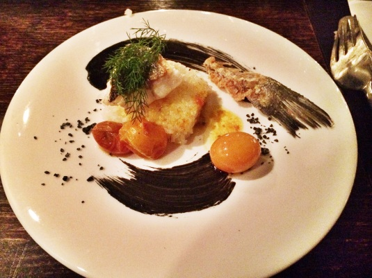 "Course 3: ""Look What the Cat Dragged In"" — black bass fillets & bones, Meyer lemon rice cakes, tomato confit, squid paint, volcanic salt"