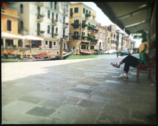 A gondolier takes a break in the heat of the Venice afternoon